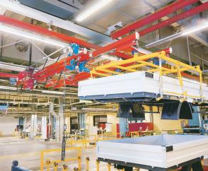 Beyond the crane runway: KBK extending crane feeds staged truck beds into the assembly line
