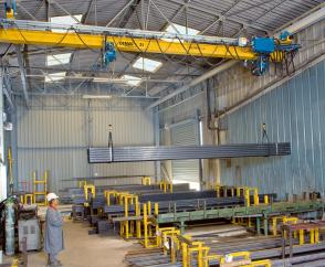 EPDE suspension cranes with rolled-profile girders and two DC-Pro chain hoists operating in tandem for handling long material in a store